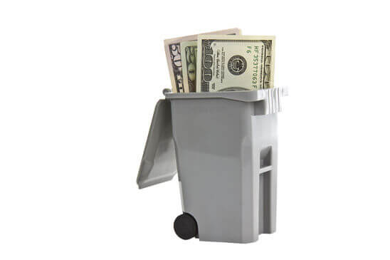 Trash bin with United States currency on white background